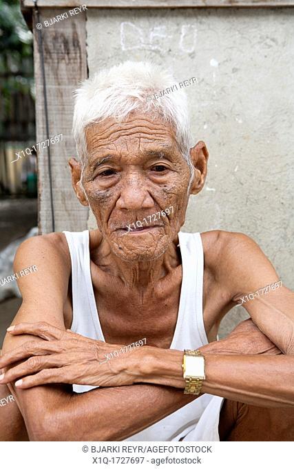 An old Filipino man sitting outside his home  Lapu-Lapu City, Metro Cebu, Mactan Island, Visayas, Philippines