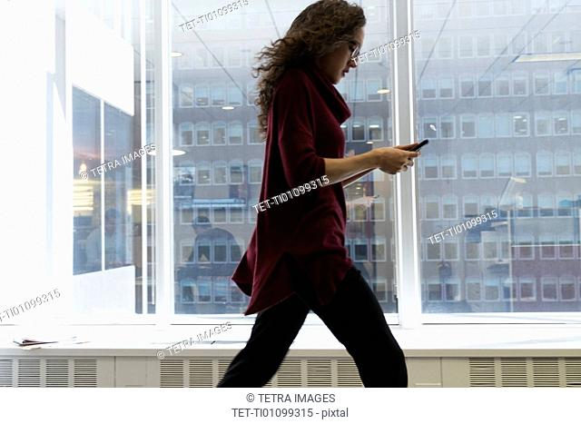 Young woman walking with mobile phone in front of window