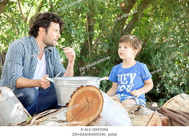 Father with young son chatting together outdoors