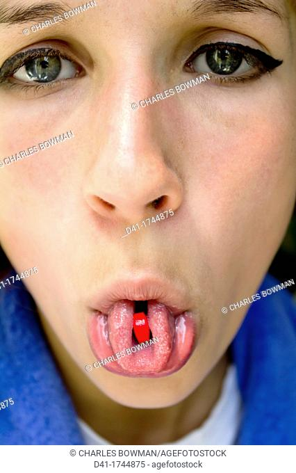 teenager with red tablet medicine