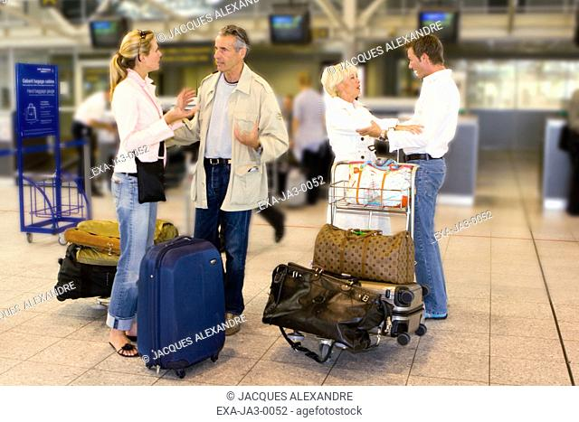 Senior couple talking to young couple with luggage at airport