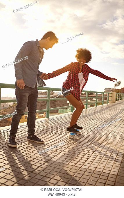 Curly haired girl learning to skateboard while holding boy holds her hand tightly in great concentration while she looks down with her arms out