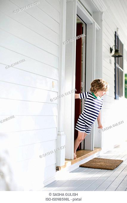 Boy leaning forward from front door onto porch