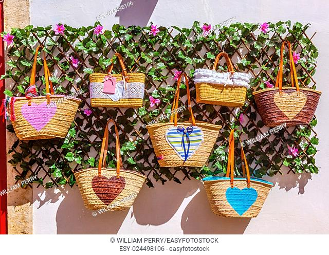 Straw Baskets Bags Colorful Handicrafts 11th Century Medieval Town Obidos Portugal. Rooster is the symbol of Portugal