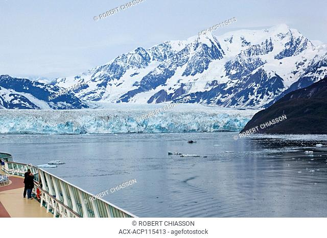 Couple on the deck of a cruise ship taking photos of Hubbard Glacier and surrounding area. Disenchantment Bay, Alaska, U.S.A