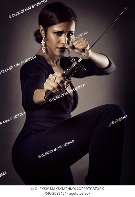 Young black woman with fierce expression in a defending pose with a Japanese Tanto knife, short sword in her hand
