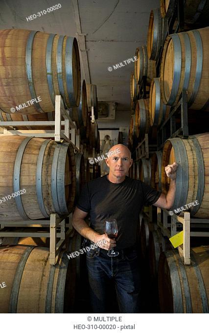 Portrait confident vintner tasting red wine in winery barrel room