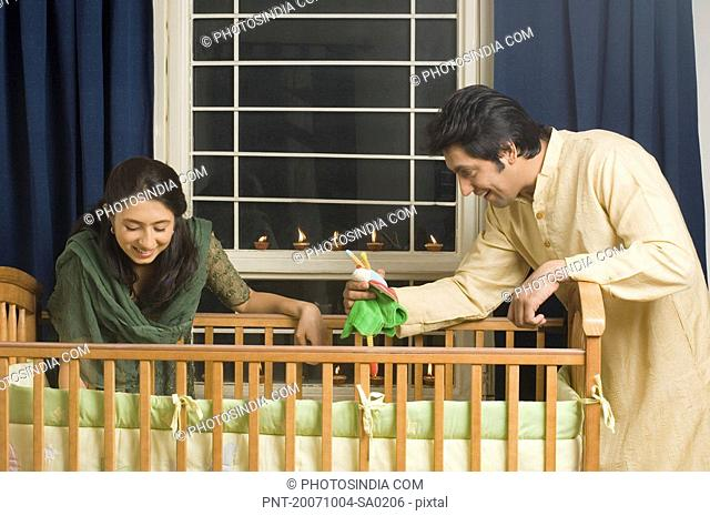 Young woman and a mid adult man looking inside a crib and smiling