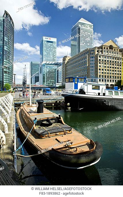 West India Quay, docklands, London, England: tugboat 'Varlet' 1935, St  Peter's Barge floating church, old cranes, modern hotel Marriott and high-rise office...