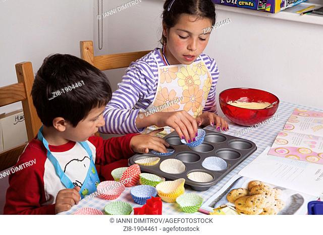 Children applying mixture to baking tin ,baking cookies together