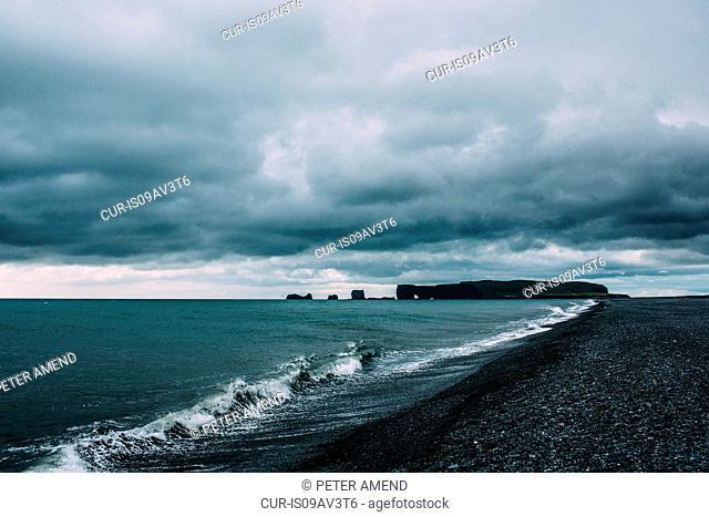 Ocean waves on coastline under dramatic sky, Vik, Iceland