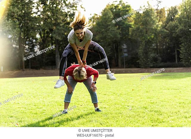 Granddaughter leapfrogging over her grandmother in a park