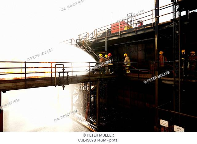 Firemen training, on training facility raised walkway spraying water on fire