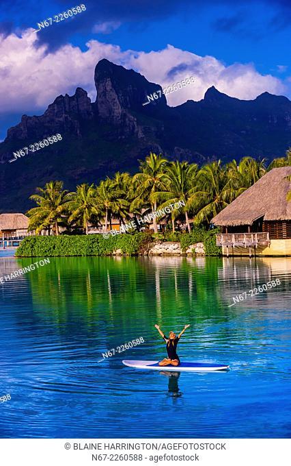 Woman doing standup paddleboard yoga in the lagoon, Four Seasons Resort Bora Bora, French Polynesia
