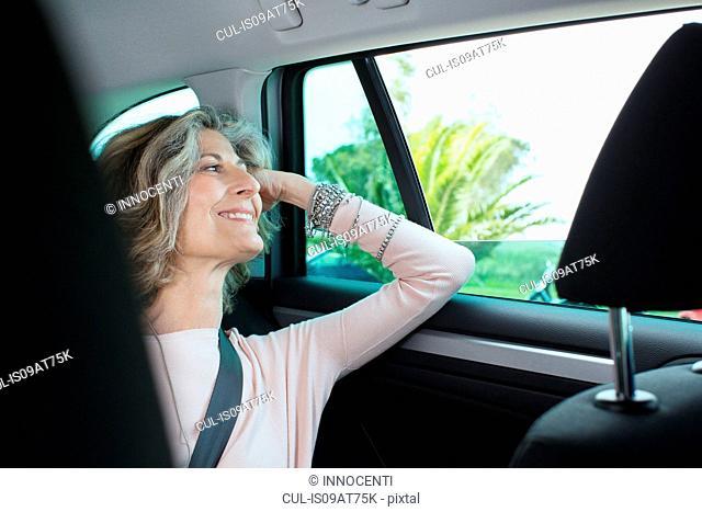 Senior businesswoman looking through car window