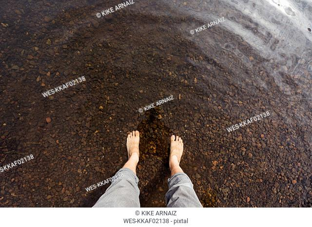 Feet of a man in water of a lake