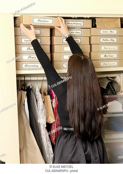 Corset maker arranging boxes in wardrobe
