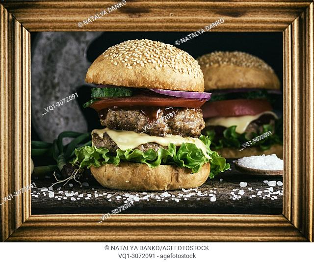 double burger with vegetables and cheese in a brown wooden frame, vintage toning