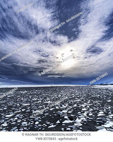 Glacial ice on a black sand beach, Breidamerkurfjara beach, Vatnajokull Ice Cap, Iceland. Large chucks of ice calve off of the Breidamerkurjokull and then wash...