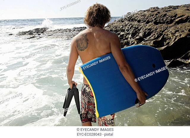 View of a man walking with a surfboard