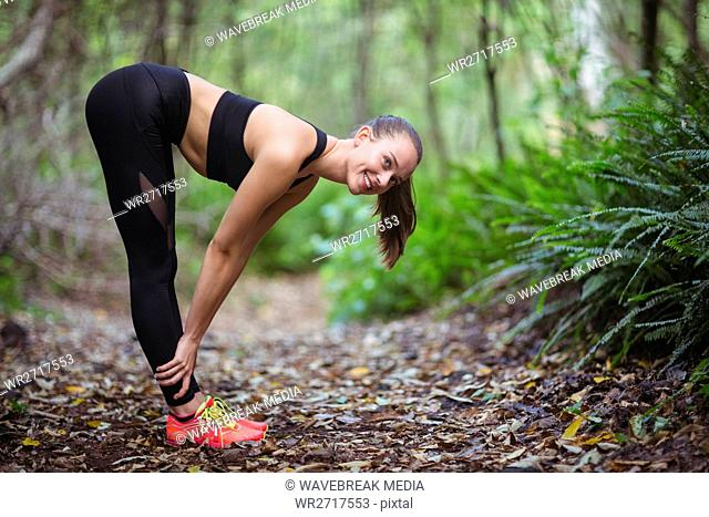 Smiling woman performing stretching exercise
