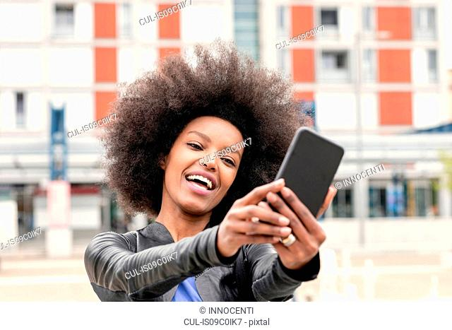 Happy young woman with afro hair in city, taking smartphone selfie