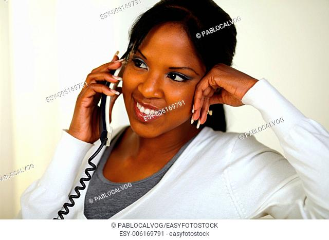Portrait of a charming relaxed woman speaking on phone at soft colors composition