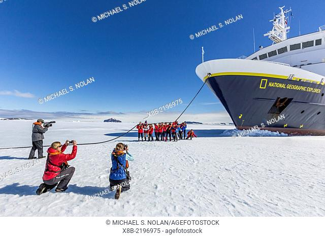 Photographer taking family photo in front of the National Geographic Explorer on first year sea ice in Duse Bay, Erebus and Terror Gulf, Weddell Sea, Antarctica