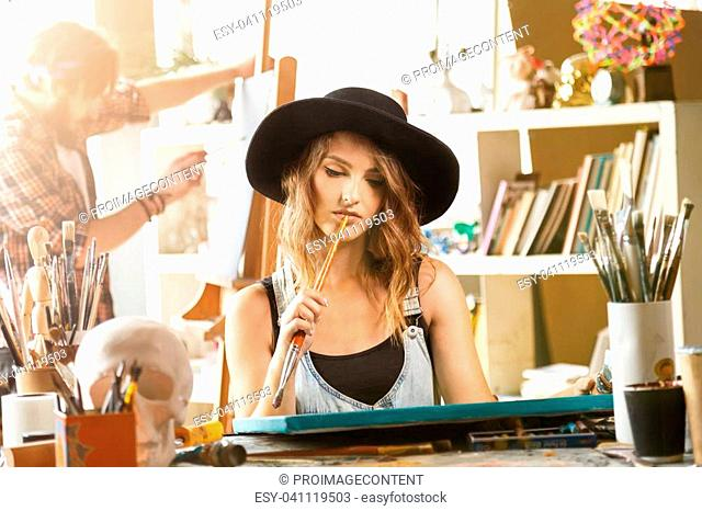 Female long hair artist in cute balck hat sitting and contemplate in light modern studio, she looking on canvas and holding brush