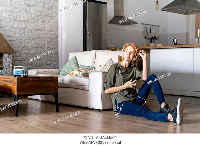 Young woman sitting on floor at home, using smartphone, wearing headphones