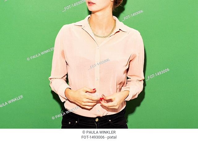 Midsection of woman in smart casuals standing against green background