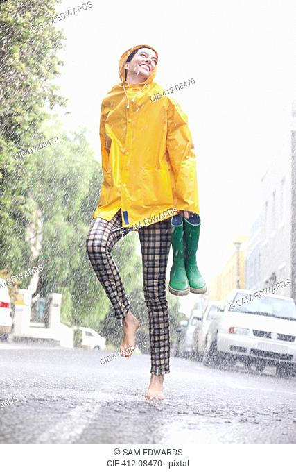 Happy woman dancing barefoot in rainy street