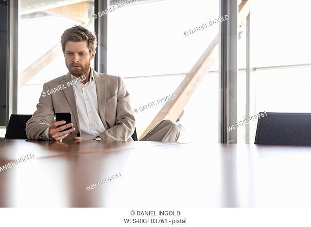 Businessman using cell phone in conference room