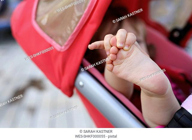 Little girl in baby buggy playing with her foot