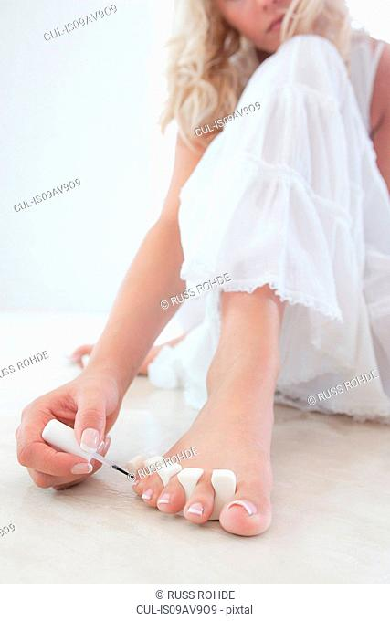 Cropped shot of young woman sitting on floor putting nail varnish on toenails