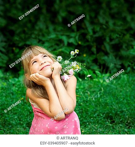 The little girl ia sitting in the green grass and dreaming