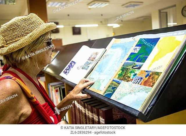 The famous national library of Fort de France in Martinique. Caucasian retired blond Woman with red top and straw hat, looking at an open book with maps and all...