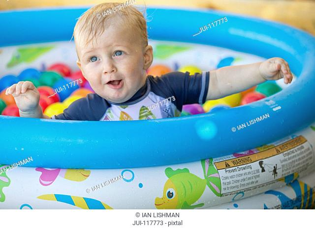 Baby Boy Playing In Outdoor Paddling Pool Filled With Balls
