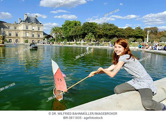 Girl playing with ship at the pond of the Palais du Luxembourg, Jardin du Luxembourg, 6th Arrondissement Latin Quarter, Paris, France