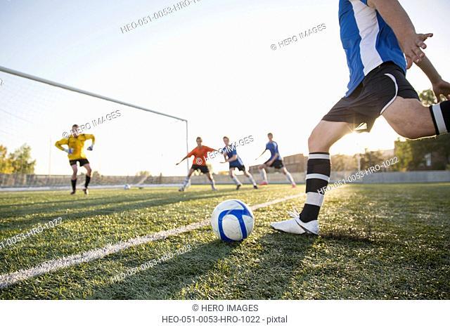 Soccer players defending net from kicker