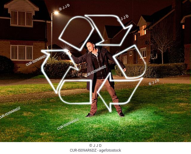 Artist light painting a recycling symbol in park