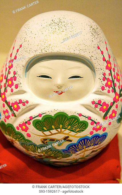 A small ceramic doll with an asian face