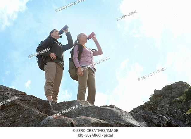 Two girl hikers drinking from flasks on top of rock formation