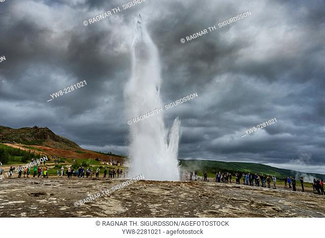 Tourist watching Strokkur Geyser erupting, Iceland. Strokkur is a fountain geyser in the geothermal area beside the Hvita River in the Haukadalur valley