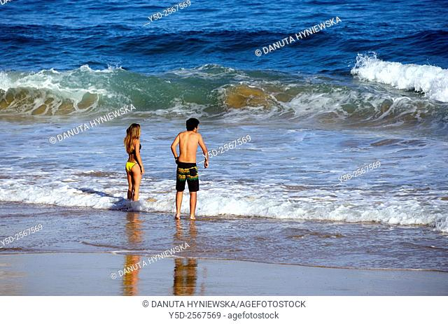 Europe, Portugal, Southern Portugal , Algarve region , Faro district , Sagres, Mareta beach - Praia da Mareta , young couple entering cold waters of Atlantic...