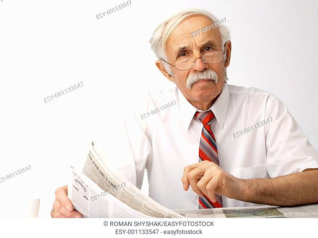 Portrait of an elder man holding an newspaper and looking at you