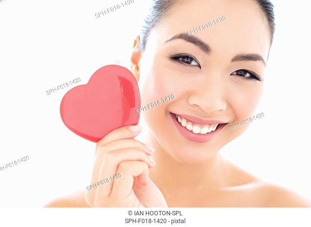 MODEL RELEASED. Young Asian woman holding heart, portrait