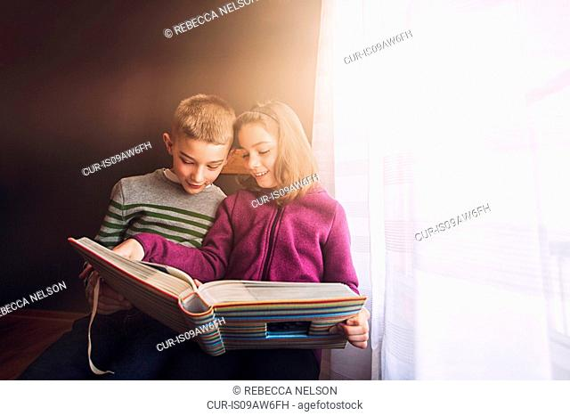 Boy and girl twins looking at photograph album next to window