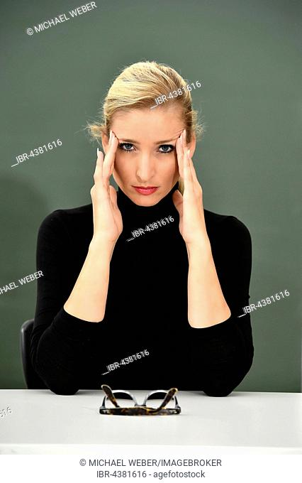 Stressed, thoughtful teacher, tutor, trainer, in front of a blackboard