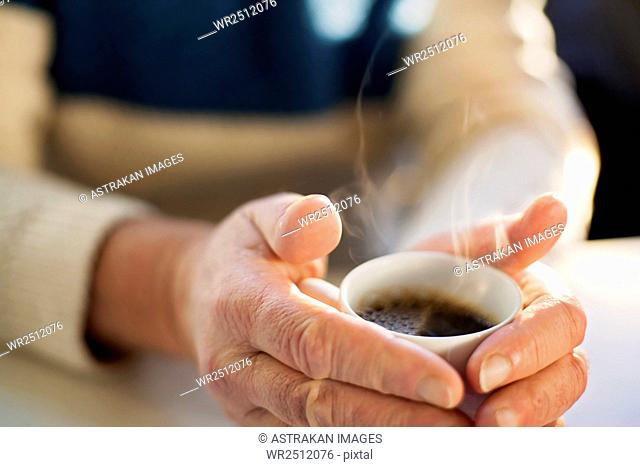 Midsection of senior man holding coffee cup at table